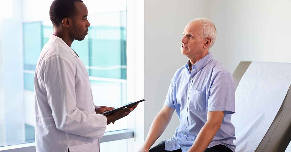 An african american doctor evaluating a caucasian elderly man in a clinic setting.
