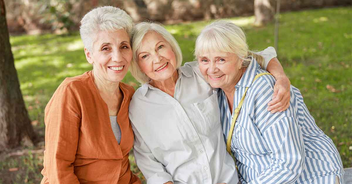 Three elderly caucasian women hugging and smiling outside, facing the camera.