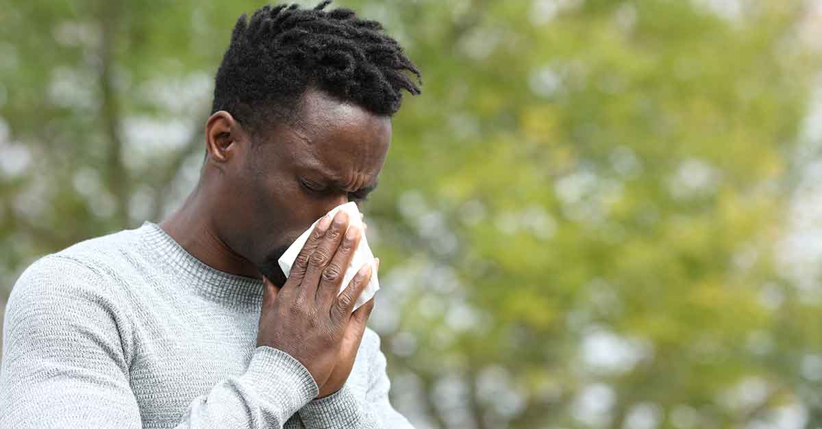 An african american man sneezing outside, into a tissue.